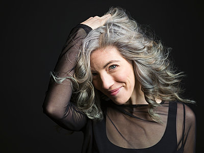 Portrait confident woman with hand in gray hair against black background - p1192m1403546 by Hero Images