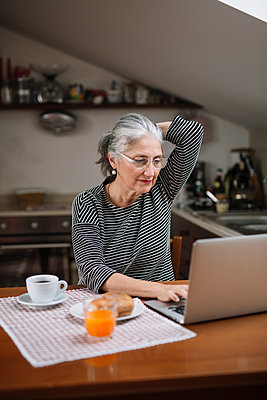 Portrait of senior woman using laptop at breakfast table - p300m2118894 by Alberto Bogo