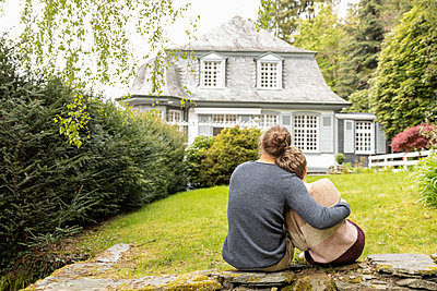 Rear view of couple sitting on a wall in garden - p300m2132369 by MiJo