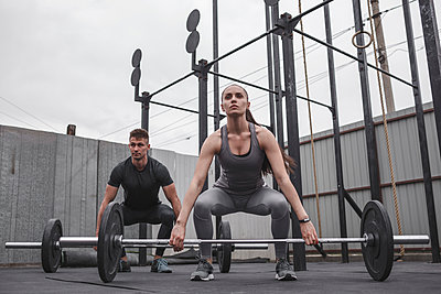 Full length of determined male and female athlete exercising with barbells during crossfit training - p301m1498798 by Vasily Pindyurin
