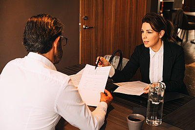 Mid adult lawyer explaining documents to mature client in meeting at law office - p426m2127776 by Maskot