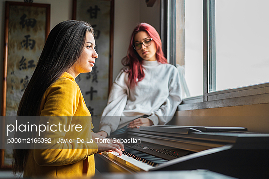 Teenage girl playing piano at home while her friend listening - p300m2166392 von Javier De La Torre Sebastian