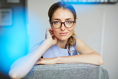 Portrait of smiling woman wearing glasses sitting on armchair - p300m1581160 von Philipp Nemenz