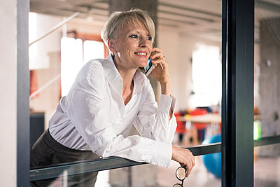 Smiling businesswoman talking on mobile phone while leaning on window at home - p300m2267761 by Robijn Page