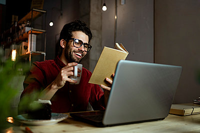 Happy businessman with laptop reading book while having coffee in illuminated cafe - p300m2276353 by Rafa Cortés