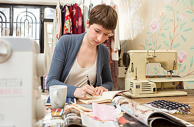 Female fashion designer drawing at her work desk - p300m998471f by Dieter Schewig
