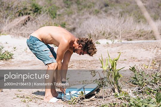 Man preparing surfboard, Sumbawa Island, Indonesia - p300m2156413 by Konstantin Trubavin