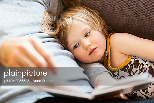 Daughter with father reading book - p312m2086395 by Anne Dillner