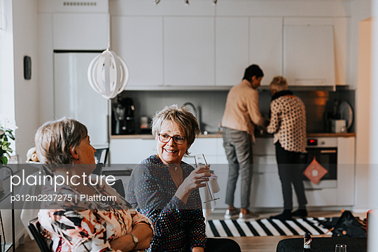 Senior friends talking together in kitchen - p312m2237275 by Plattform