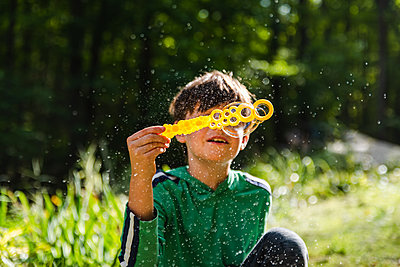 Young boy blowing soap bubbles with a large wand outdoors. - p1166m2214640 by Cavan Images