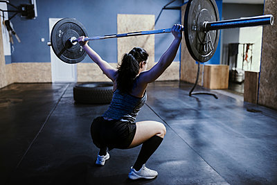 Woman lifting barbell in gym - p300m1581507 by Zeljko Dangubic