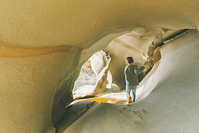Little boy exploring sandstone caves - p300m2102725 by Crystal Sing