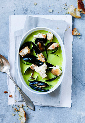 Bowl of pea and mussels soup - p429m746984f by Line Klein