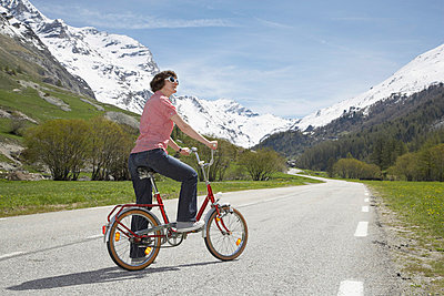 Woman with red bike in France - p4641148 by Elektrons 08