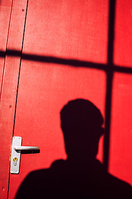 Shadow of a mysterious man on a red door  - p794m1135039 by Mohamad Itani