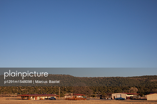 Ranch houses at sunset against low wooded hills - p1291m1548098 by Marcus Bastel
