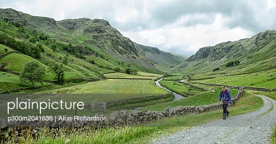 UK, Lake District, Longsleddale valley, mature man walking on field path in rural landscape - p300m2041636 von Alun Richardson