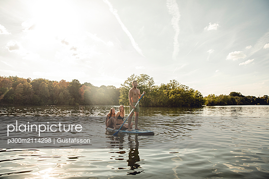 Friends enjoying summer on the lake, paddling on a paddleboard - p300m2114298 von Gustafsson