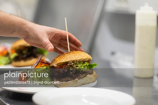 Fast food worker preparing hamburger and salad in commercial kitchen, close up of hand - p429m2069473 by Sigrid Gombert
