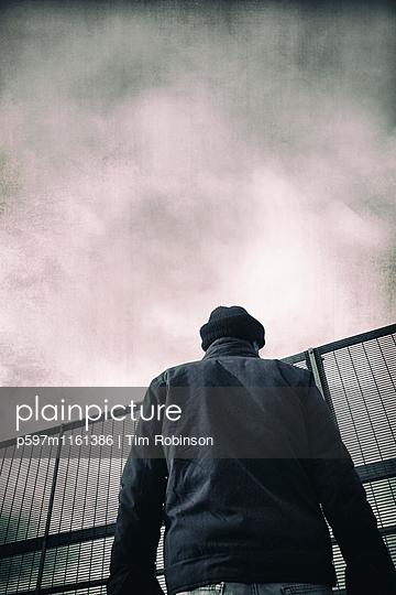 Rückansicht eines Mannes vor einem Metallzaun - p597m1161386 von Tim Robinson