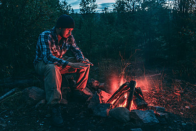 Man sitting at campfire in rural landscape - p300m1537421 by Vasily Pindyurin