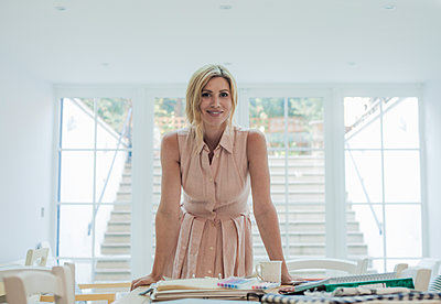 Portrait of female entrepreneur standing near fabric swatches and fashion designs on table - p300m2140087 by LOUIS CHRISTIAN