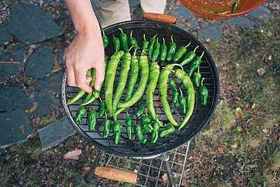 High angle detail of man grilling peppers on barbecue - p301m1180548 by Halfdark