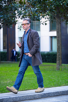 Man with smartphone and earbuds walking outdoors - p429m1417835 by RUSS ROHDE