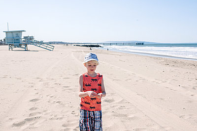 Boy on sunny sandy beach, wearing sunglasses and hat - p924m2271154 by Viara Mileva