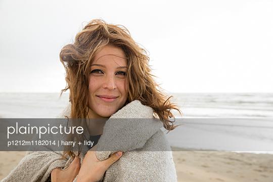 Junge Frau am Strand - mit Decke  - p1212m1182014 von harry + lidy