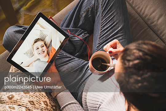 Mature woman holding coffee cup while video call on digital tablet at home - p300m2243545 by Uwe Umstätter
