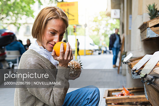 Woman smelling fruit while crouching at street market - p300m2286799 by NOVELLIMAGE