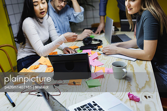 Four people using digital tablet at desk in creative office - p426m1407161 by Maskot