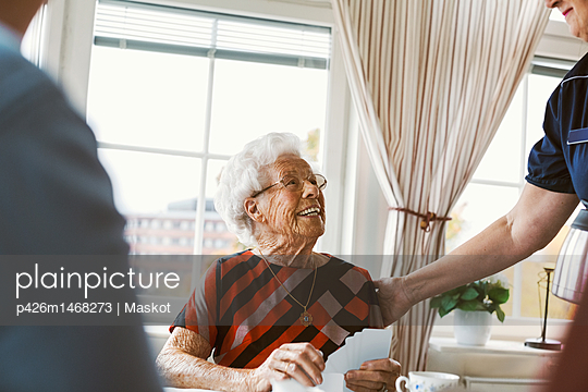 Happy senior woman looking at caretaker while playing cards with family - p426m1468273 by Maskot