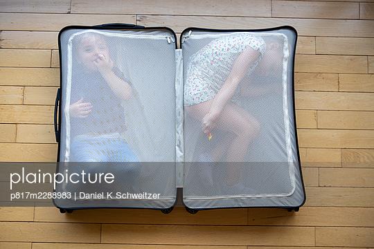 Boy and girl hiding in a suitcase - p817m2288983 by Daniel K Schweitzer