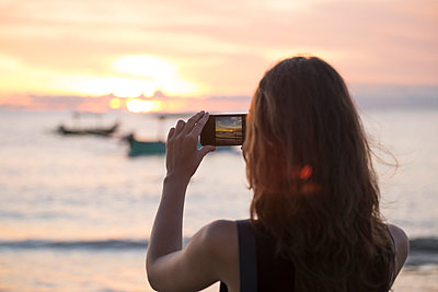 Indonesia, Bali, woman taking a picture of the sunset over the ocean - p300m1356505 by Konstantin Trubavin