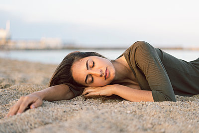 Beautiful woman relaxing on the beach at sunset, portrait - p300m2024052 von VITTA GALLERY