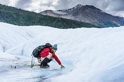Male hiker collects water from glacial stream on Glacier Wrangell - p343m1475640 by Cavan Images