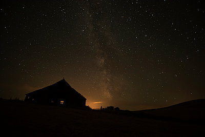 Night sky glowing over silhouette of a barn with a peaked roofline; Palouse, Washington, United States of America - p442m1180003 by Marg Wood