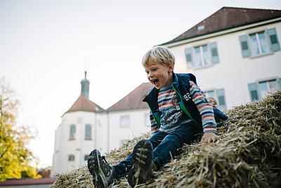 Kleiner Junge auf Heuhaufen - p819m1128396 von Kniel Mess