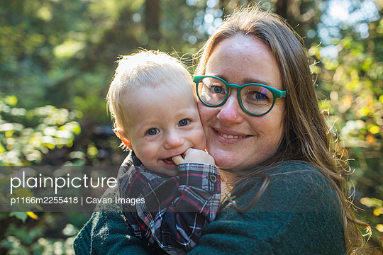 Outdoor portrait of a mother holding her one year old son. - p1166m2255418 by Cavan Images