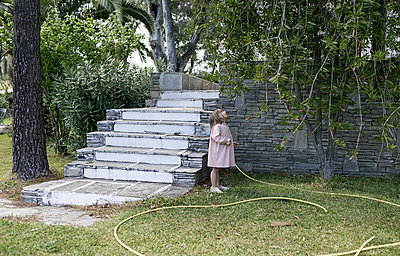 Little girl standing in garden looking up to tree - p300m1587964 by Katharina Mikhrin