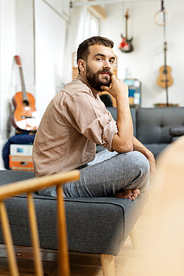 Young man sitting cross-legged on couch at home - p300m2166982 by Peter Scholl
