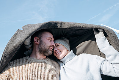Portrait of mature couple hiding under  coat - p300m2180720 by Katharina und Ekaterina