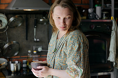 Woman looking away holding tea cup in kitchen at home - p300m2275120 by Ekaterina Yakunina