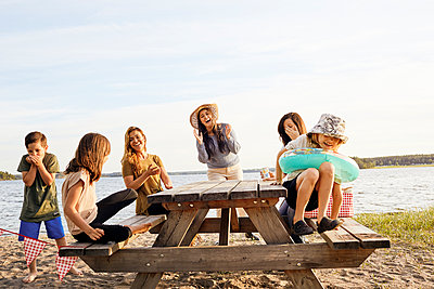 Family having picnic at lake - p312m2299486 by Plattform