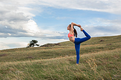 Athletic female yogi in dancer pose outside in a field in Boulder, Colorado - p343m1168452 by Alexandra Simone