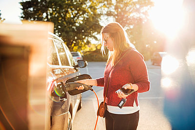 Woman holding smart phone while charging electric car at station on sunny day - p426m1212724 by Maskot