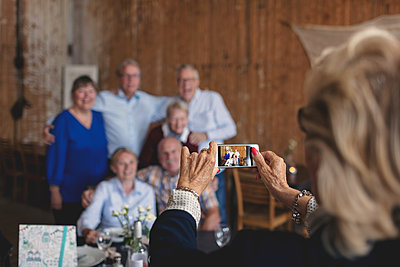 Senior woman photographing happy friends sitting at table in restaurant - p426m1506298 by Maskot