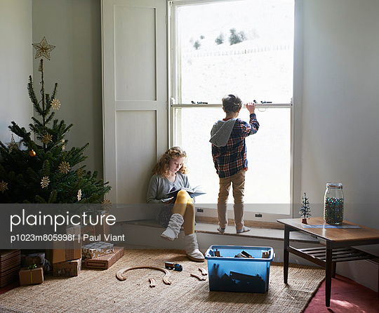 Children in living room with Christmas tree - p1023m805998f by Paul Viant